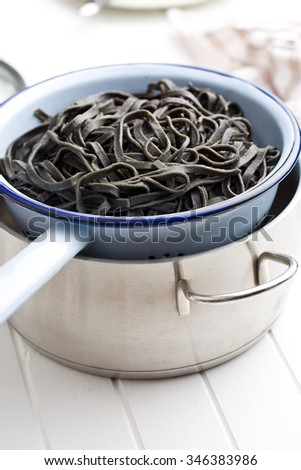cooked black noodles with squid sepia ink in colander - stock photo