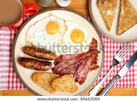 Cooked breakfast with toast and a mug of tea. - stock photo