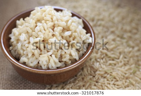 cooked brown rice and rice grains on jute cloth. organic. - stock photo