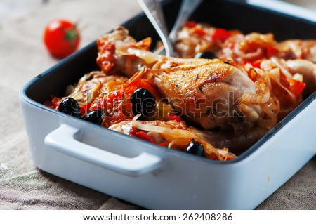 Cooked chicken with tomato, onion, pepper and olive on the table, selective focus - stock photo