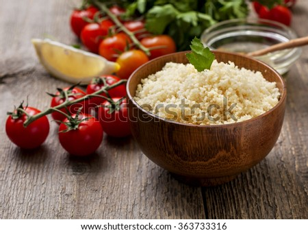 cooked couscous, fresh vegetables for salad: tomatoes, lemon, parsley and olive oil on a wooden background - stock photo
