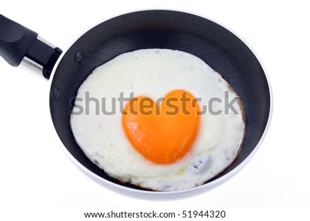 cooked egg - heart form in a fryer isolated on white - stock photo