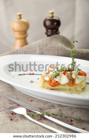Cooked fish fillet with tomatoes and white sauce on the table - stock photo