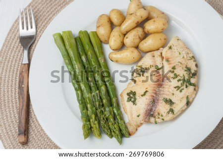 cooked fish with parsley servied with asparagus and baby potatoes on white plate, top view - stock photo
