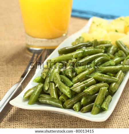 Cooked green beans with onion and parsley with cooked potato, orange juice and blue napkins in the back (Selective Focus, Focus on one third of the picture) - stock photo