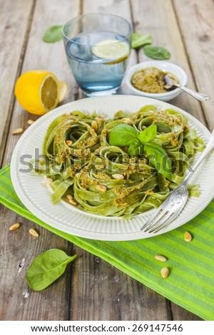 Cooked homemade spinach pasta with pesto, pine nuts and basil leaves served over the rustic wooden table - stock photo