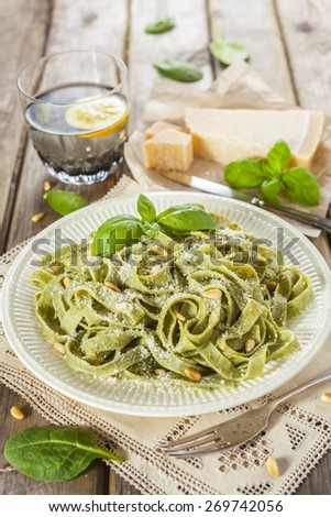 Cooked homemade spinach pasta with pesto, pine nuts, Parmesan cheese and basil leaves over the rustic wooden table - stock photo