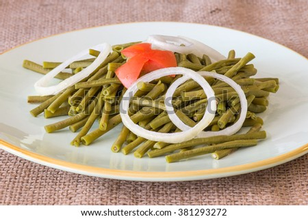 Cooked long Chinese green beans. Delicious salad that only uses oil and vinegar as dressing. The plate is garnished with a star of tomato and white onion rings. - stock photo