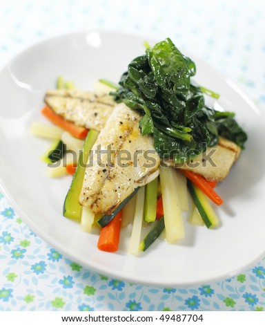 cooked mackerel fish meal with spinach on the top. Carrot and zukini below. Very shallow depth of field. - stock photo