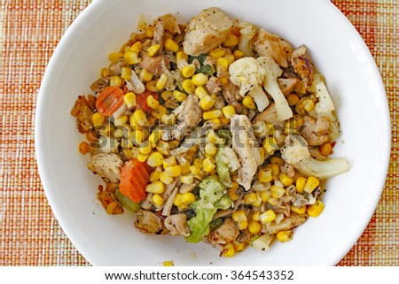 Cooked meal of chicken, carrots, broccoli, cauliflower and corn with pepper served in a round white bowl on a colorful placemat. Chicken and mixed vegetables supper.