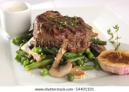 cooked meat on a plate with sauce and greens