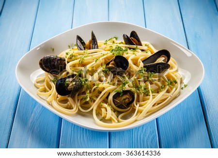 Cooked mussels and pasta on white background  - stock photo