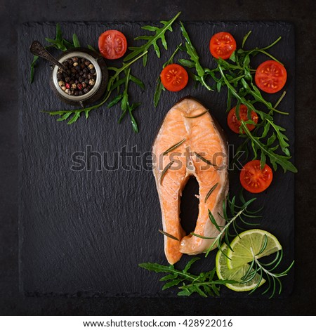 Cooked on steam salmon steak with vegetables on black background. Dietary menu. Proper nutrition. Top view - stock photo
