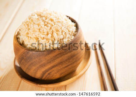 Cooked organic basmati brown rice in wooden bowl with chopsticks on dining table. - stock photo