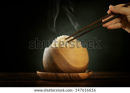 Cooked organic basmati brown rice in wooden bowl with human hand chopsticks and hot steam smoke on dining table. Low light setting. - stock photo