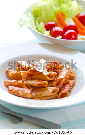 Cooked penne pasta and fresh salad - stock photo