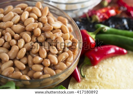 Cooked pinto beans and other ingredients for Mexican cooking. - stock photo