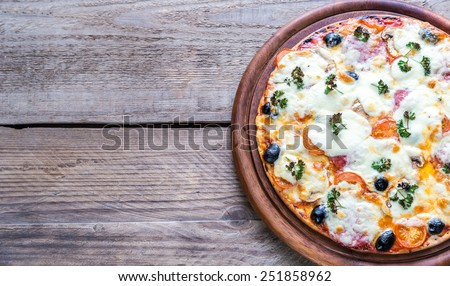 Cooked pizza on the wooden board - stock photo