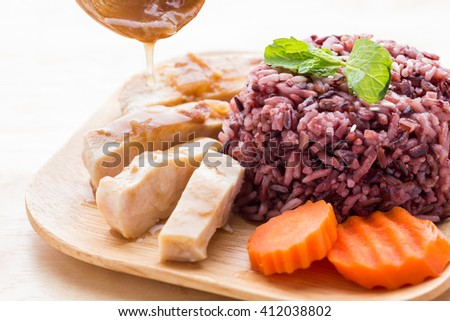 Cooked purple rice berry with roasted chicken breast and carrot in wooden plate with peppermint leaves; clean food; healthy eating. - stock photo