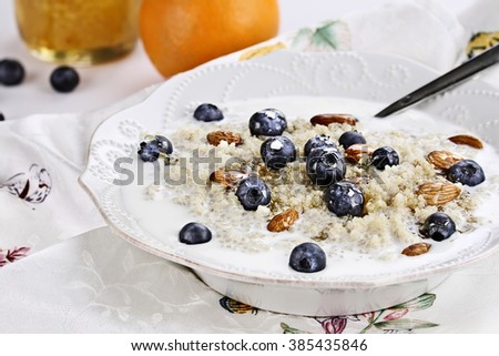 Cooked Quinoa with blueberries, almonds and honey. Selective focus with extreme shallow depth of field. - stock photo