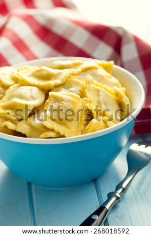 cooked ravioli in bowl on kitchen table - stock photo
