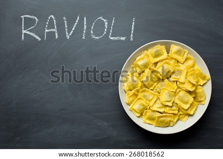 cooked ravioli pasta on chalkboard - stock photo