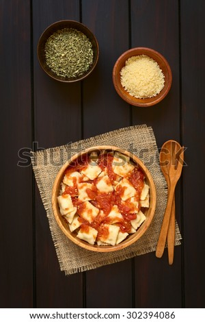 Cooked ravioli with homemade tomato sauce in wooden bowl with grated cheese and dried oregano in small bowls, wooden spoon and fork on the side, photographed overhead on dark wood with natural light - stock photo