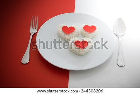 cooked rice heart shapes with a spoon and fork on white dish  half of red and white background