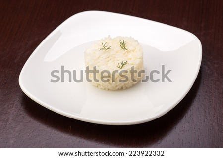 Cooked rice on the plate on wooden table
