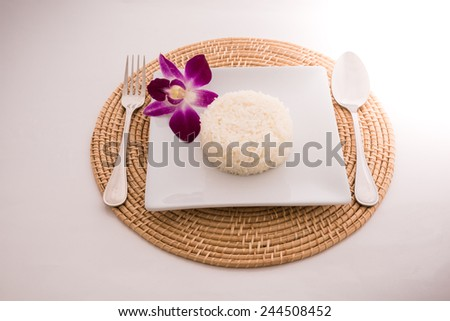 cooked rice with a spoon and fork on white dish in Platemat and orchid on white background
