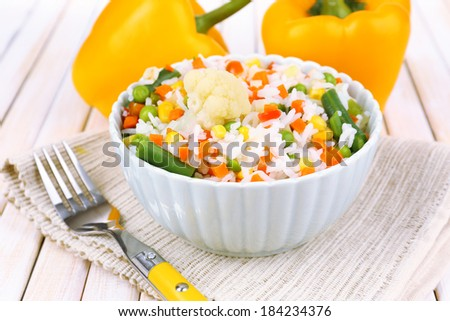 Cooked rice with vegetables on wooden table close up - stock photo