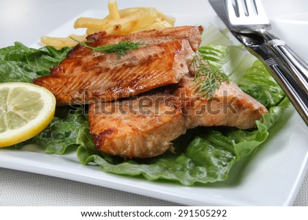 Cooked salmon file on a white plate, shallow focus - stock photo