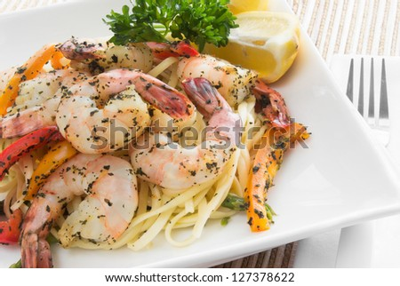 Cooked shrimp with the tail on served on a bed of linguini pasta and prepared with basil, lemon, asparagus and bell pepper. A square white ceramic plate holds the food.  - stock photo