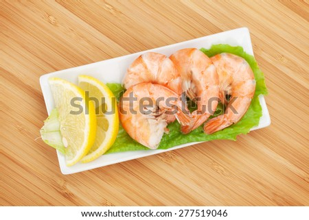 Cooked shrimps with lemon and salad leaves. View from above on wooden table - stock photo