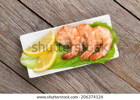 Cooked shrimps with lemon. View from above on wooden table - stock photo