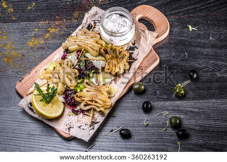 cooked squid on skewers, squid rings - stock photo