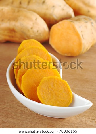 Cooked sweet potato (lat. Ipomoea batatas) cut in slices in white bowl on wooden surface with sweet potatoes in the background (Selective Focus, Focus on the front of the bowl) - stock photo