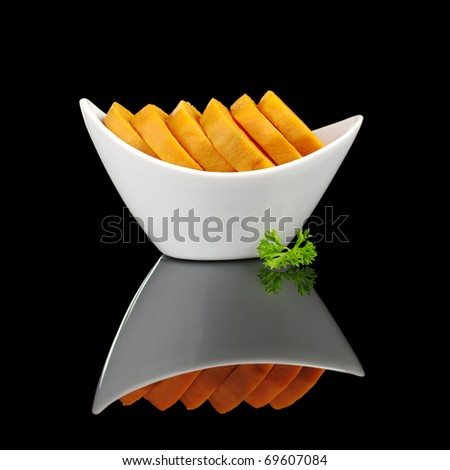 Cooked sweet potato slices (lat. Ipomoea batatas) in white bowl garnished with a parsley leaf and photographed on black  (Selective Focus, Focus on the front) - stock photo