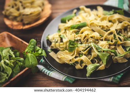 Cooked tagliatelle pasta with greens and grated parmesan cheese - stock photo