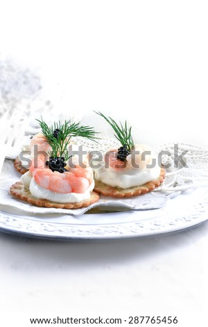 Cooked Tiger prawn, caviar and cream cheese canapes in a vintage setting against a white, bright background with copy space. The perfect image for your wedding reception cover image. - stock photo