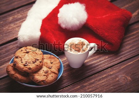 Cookie and cup of coffee with santa's hat on wooden table. Photo in retro color image style. - stock photo