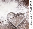 Cookie cutter heart shape on the kitchen table and flour - stock photo