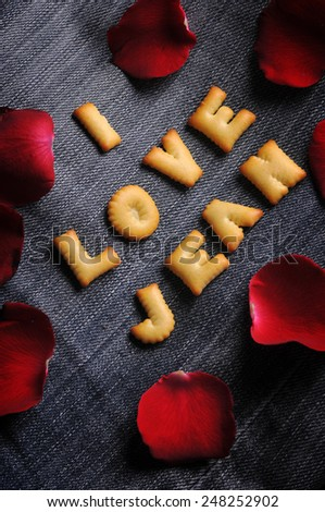 Cookies ABC in the form of word I LOVE JEAN alphabet with red rose petal on old jean background, Valentines day - stock photo