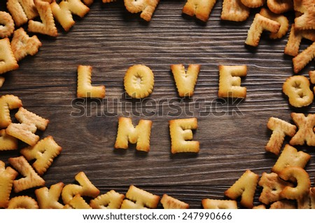 Cookies ABC in the form of word LOVE ME alphabet on old wood background, Valentines day - stock photo