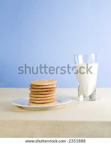 Cookies and milk on blue background - stock photo