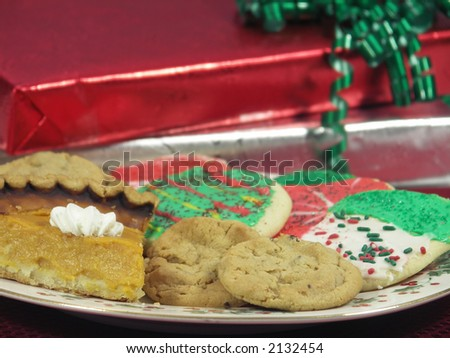 Cookies and pie on a plate with wrapped gifts. Shallow DOF. - stock photo