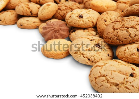 Cookies background. Sweet chocolate chips biscuits heap isolated at white background with copy space. Oatmeal, chocolated drops and other sweets closeup - stock photo