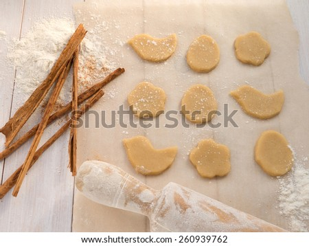 Cookies, cinnamon sticks and roller-pin - stock photo