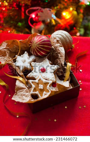 cookies in a gift box on the background of the Christmas tree - stock photo