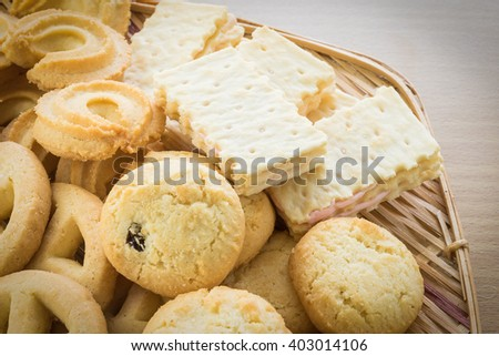 Cookies in bamboo bowl on wood table background - stock photo